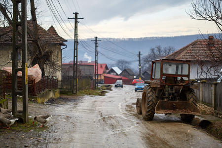 Old tractor parked near a house in a village