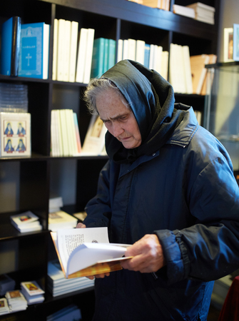 Old woman picking a religious book from churchs library