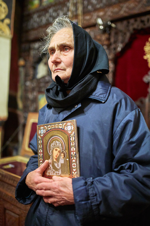 Old peasant woman holding a religious icon inside a church Banque d'images