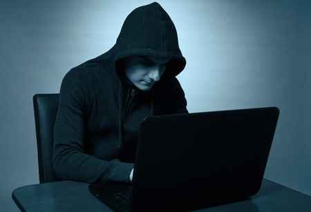 Hooded hacker at laptop, operating incognito Stock Photo