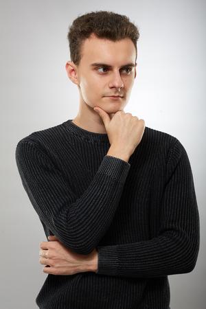 Jeune homme pensif avec la main sur le menton, perdu dans ses pensées