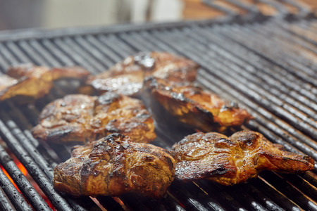 Pork neck getting grilled outdoors