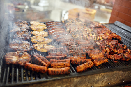 Variety of meat getting grilled outdoors