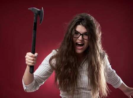Enraged businesswoman wielding a hatchet ready to attack