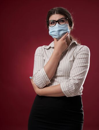 Unsure businesswoman in face mask and glasses over red background