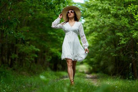 Gorgeous beauty model in summer dress posing outdoor in an oak forest