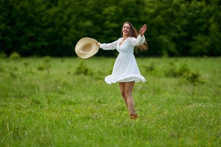 Gorgeous beauty model in summer dress dancing outdoor in an oak forest