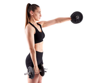 Young hispanic athletic woman doing shoulders workout with dumbbells on white background