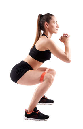 Athletic woman working out with elastic bands isolated on white background