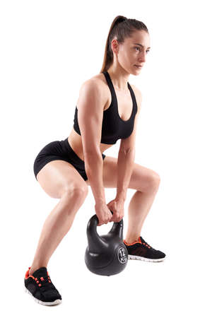 Young athletic woman doing workout with kettlebell isolated on white background