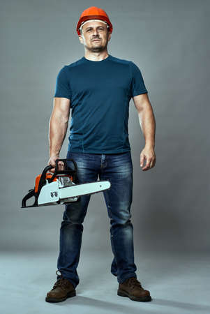 Worker in hardhat holding a chainsaw medium size Stock Photo