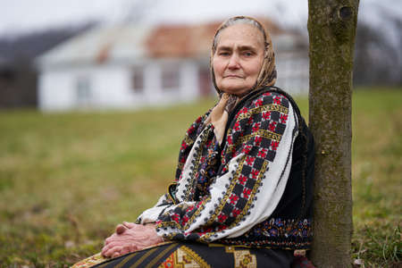 Old Romanian woman in popular national costume sitting on a chair in her garden