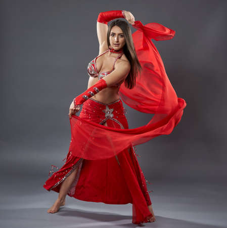 Arab woman belly dancer in red sparkling costume on gray background Banco de Imagens