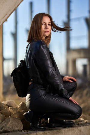 Post apocalyptic portrait of a beautiful young woman in black leather at a ruined industrial facility