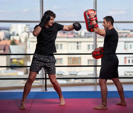 Young kickboxing fighter hitting mitts with his coach in the gym