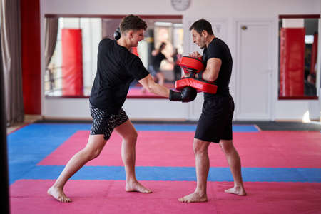 Young kickboxing fighter hitting mitts with his coach in the gym Stock Photo