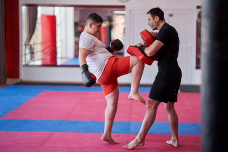 Overweight kickbox fighter hitting mitts with his coach