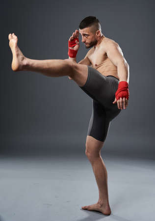 MMA fighter throwing a leg kick, studio shot isolated on gray background Foto de archivo