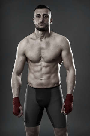 MMA fighter in training, posing for a shot oni gray background