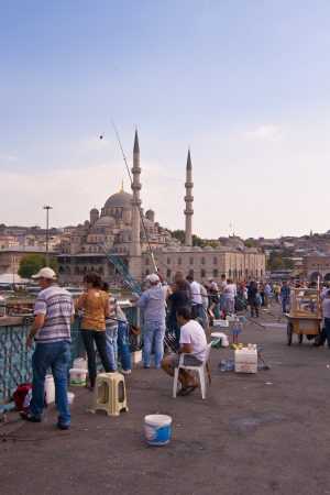 Men fishing on Galata Bridge which spans the Golden Horn in Istanbul, Turkey.There behind the Galata Tower