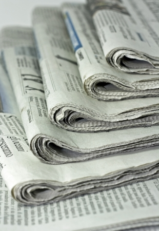 periodical: newspapers against plain background shot with very shallow depth of field