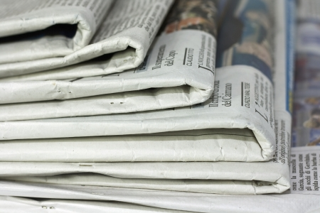 breaking news: newspapers against plain background shot with very shallow depth of field