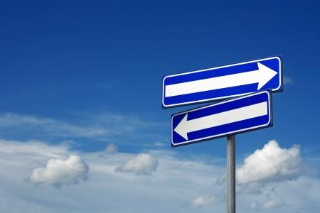 cruce de caminos: firmar doble camino - cielo azul Foto de archivo