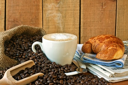 cappuccino, croissants and newspaper with background photo