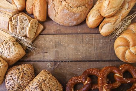 comiendo pan: Diferentes tipos de pan en el fondo de madera Foto de archivo