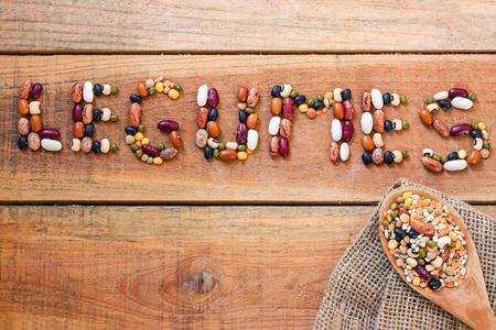 leguminosas: Las legumbres palabra con fondo de madera - los alimentos