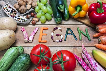 intolerancia: vegano de la palabra en el fondo de madera y vegetales - alimentos Foto de archivo