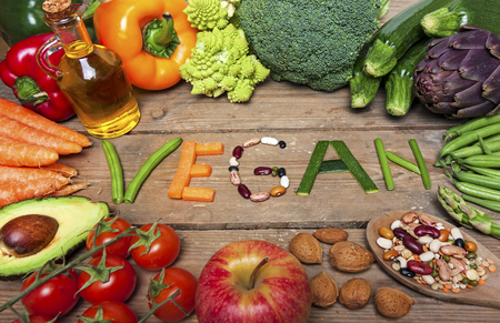 vegan word on wood background and vegetable - food