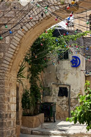 Narrow cobbled street among traditional stoned houses of jewish quarter at old historic part of jerusalem, Israel. Stock Photo