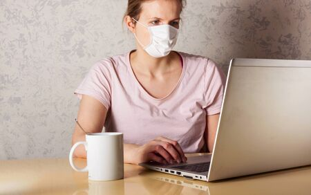 Coronavirus. Young business woman working from home wearing protective mask. Business woman in quarantine for coronavirus wearing protective mask. Working from home. Stock Photo