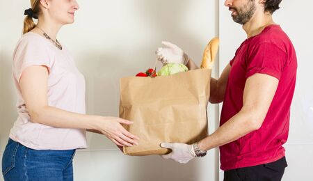 smart food delivery service man in red uniform handing fresh food to recipient and young woman customer receiving order from courier at home, express delivery, food delivery, online shopping concept Reklamní fotografie