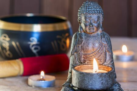 stone sitting buddha, candles and Tibetan bowl. Around the candle, the atmosphere for meditation. Home comfort and relaxation