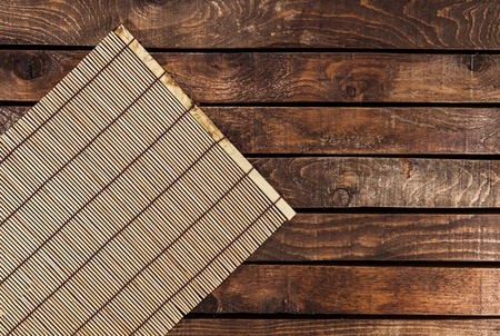 Bamboo tablecloth on wooden table over grunge background. Ready for product display montage