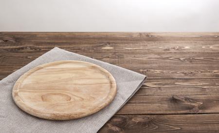 製品のモンタージュの背景。テーブル クロスをかけた空の丸い木の板。
