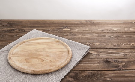 Background for product montage. Empty round wooden board with tablecloth.