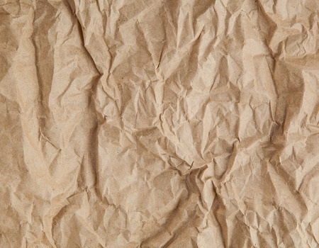 disheveled: crumpled cream color tone paper pattern texture background in sepia light.bright creased plain backdrop concept.vintage scruffy disheveled wallpaper conception.empty edge parchment paper sheet wall.