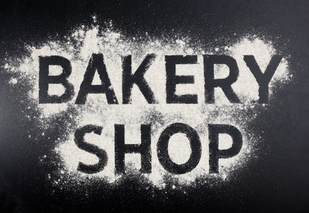 bake sale sign: Bakery shop word made of flour on black table.