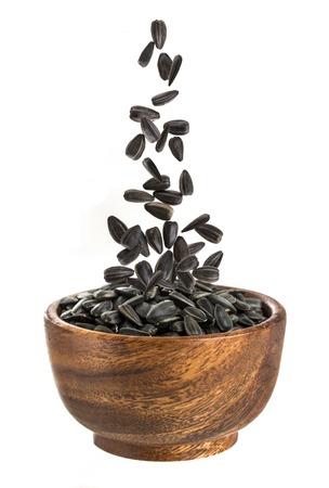 Semi di girasole in una ciotola di legno. Caduta semi di girasole su uno sfondo bianco