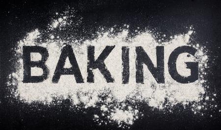 white flour: Baking word made from white flour on dark table, baking store logo.
