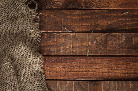 sacco juta: tessitura della tela da sullo sfondo della tabella di legno. Tavolo in legno con saccheggio