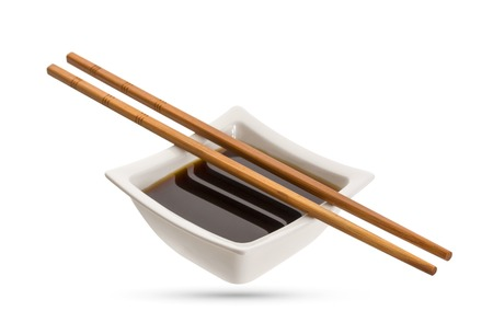 Bowl of soy sauce and chopsticks isolated on white background Фото со стока