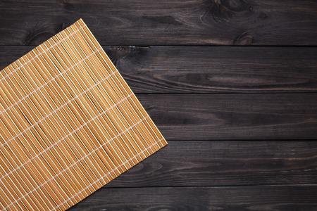 暗い木製のテーブル、上面にオレンジ色の竹ナプキン