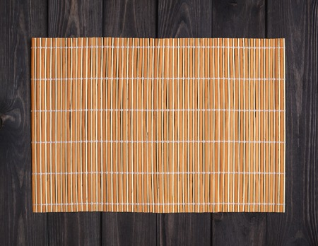 orange bamboo napkin on a dark wooden table, top view Stock Photo