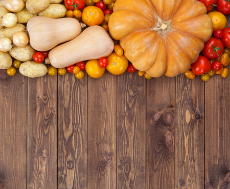 red onions: Autumn harvest on wooden table background. Pumpkin, zucchini, potatoes, onions and other vegetables