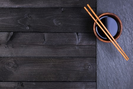 Background for sushi. Soy sauce, chopsticks on black stone. Top view with copy space Reklamní fotografie