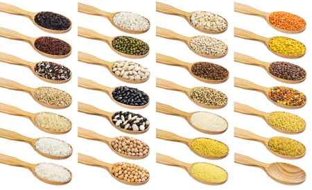 Collection of different groats in wooden spoons isolated on white background. Imagens